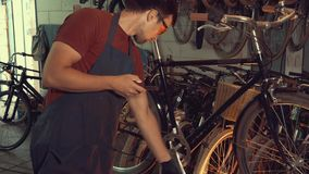 Theme small business bike repair. Young caucasian brunette man wearing safety goggles, gloves and fartukhe uses mobile