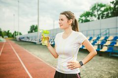Theme is sport and health. Beautiful young caucasian woman with big breasts athlete runner stands resting on running. Stadium, running track with bottle in royalty free stock photo
