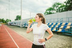 Theme is sport and health. Beautiful young caucasian woman with big breasts athlete runner stands resting on running. Stadium, running track with bottle in royalty free stock image