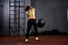 Theme sport and health. A strong muscular Caucasian woman in the gym trains strength and endurance. Equipping a large printed. Black ball raises and throws over stock photo