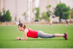 Theme sport and health. Young Caucasian woman doing warm-up, warming up muscles, training abdominal muscles. Losing belly. royalty free stock photos