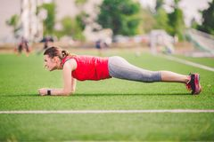 Theme sport and health. Young Caucasian woman doing warm-up, warming up muscles, training abdominal muscles. Losing belly. stock photos