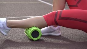 Theme sport and rehabilitation sports medicine. Beautiful strong slender Caucasian woman athlete sits next foam roller green field stock video footage