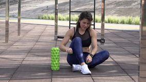 Theme sport and rehabilitation sports medicine. Beautiful strong slender Caucasian woman athlete sits next foam roller green field stock footage