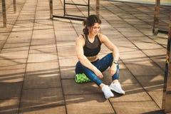 Theme sport and rehabilitation sports medicine. Beautiful strong slender Caucasian woman athlete sits next foam roller green field stock photo