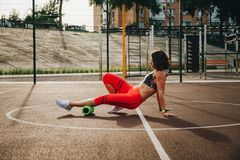 Theme sport and rehabilitation sports medicine. Beautiful strong slender Caucasian woman athlete uses foam roller green field stre stock images