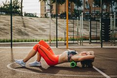 Theme sport and rehabilitation sports medicine. Beautiful strong slender Caucasian woman athlete uses foam roller green field stre stock photography