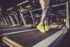 Theme of sport and weight loss. Close-up of the foot of a young strong woman in a light green sneakers on a simulator, running in. The gym. Preheating before Royalty Free Stock Photo