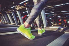 Theme of sport and weight loss. Close-up of the foot of a young strong woman in a light green sneakers on a simulator, running in. The gym. Preheating before Royalty Free Stock Images