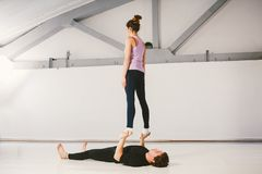 Theme is sports and acreage. A young Caucasian male and female couple practicing acrobatic yoga in a white gym on mats. a man lies royalty free stock image