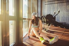 Theme sports, health and technology. beautiful Caucasian woman sportswoman in gray sportswear and hat sits by window with sun royalty free stock photo