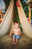 Theme summer vacation, little boy, Caucasian child playing in wooded area in park on playground in yard. kid in Tipi wigwam tent. Theme summer vacation, little royalty free stock photos