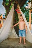 Theme summer vacation, little boy, Caucasian child playing in wooded area in park on playground in yard. kid in Tipi wigwam tent royalty free stock photo