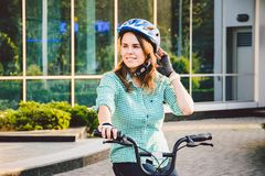 Theme to work on the bike. A young Caucasian woman arrived on environmentally friendly transport bike to the office. Girl in a bic. Ycle parking office building stock photography
