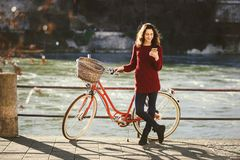 Theme tourism on bicycle and modern technology. Beautiful young caucasian woman stands near red retro bicycle on riverside river R Stock Photos