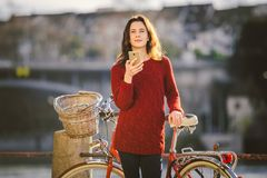 Theme tourism on bicycle and modern technology. Beautiful young caucasian woman stands near red retro bicycle on riverside river R Royalty Free Stock Photography