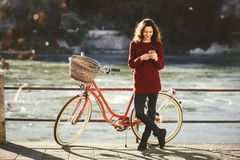 Theme tourism on bicycle and modern technology. Beautiful young caucasian woman stands near red retro bicycle on riverside river R Royalty Free Stock Image