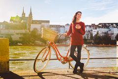 Theme tourism on bicycle and modern technology. Beautiful young caucasian woman stands near red retro bicycle on riverside river R Stock Images