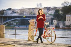 Theme tourism on bicycle and modern technology. Beautiful young caucasian woman stands near red retro bicycle on riverside river R Royalty Free Stock Photos
