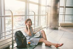 Theme of tourism and travel of young student. Beautiful young caucasian girl in dress and hat sits on floor tourist rug inside royalty free stock photography