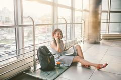 Theme of tourism and travel of young student. Beautiful young caucasian girl in dress and hat sits on floor tourist rug inside stock photography