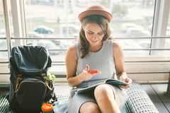 Theme of tourism and travel of young student. Beautiful young caucasian girl in dress and hat sits on floor tourist rug inside stock photos