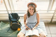 Theme of tourism and travel of young student. Beautiful young caucasian girl in dress and hat sits on floor tourist rug inside royalty free stock images