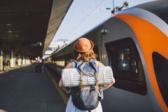 Theme transportation and travel. young caucasian woman standing at train station platform near train backs train background with. Backpack travel mat sleepy royalty free stock image