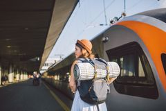 Theme transportation and travel. young caucasian woman standing at train station platform near train backs train background with. Backpack travel mat sleepy stock photo