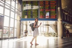 Free Theme Travel And Tranosport. Beautiful Young Caucasian Woman In Dress And Backpack Standing Inside Train Station Or Terminal Looki Stock Photography - 124980362