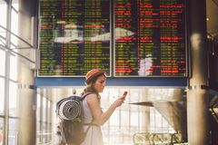 Theme travel and tranosport. Beautiful young caucasian woman in dress and backpack standing inside train station or terminal looki. Ng at a schedule holding a stock image