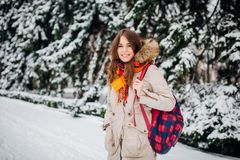 Theme is weekend holiday in winter. A beautiful young Caucasian woman stands in snow park in jacket with hood and fur in jeans and. Smiles with checkered Royalty Free Stock Photos