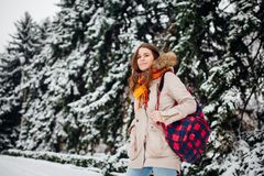 Theme is weekend holiday in winter. A beautiful young Caucasian woman stands in snow park in jacket with hood and fur in jeans and. Smiles with checkered Royalty Free Stock Image