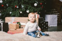 Theme winter and Christmas holidays. Child boy Caucasian blond 1 year old sitting home floor near Christmas tree with New Year dec. Or on shaggy carpet skin royalty free stock photos