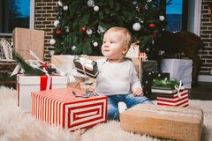 Theme winter and Christmas holidays. Child boy Caucasian blond 1 year old sitting home floor near Christmas tree with New Year dec royalty free stock images