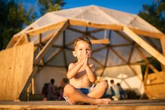 Theme yoga and children. Caucasian Boy in blue shorts child sits barefoot with his legs crossed in lotus pose and waving. His arms with smile on wooden floor Stock Image