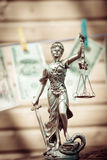 Themis女神或夫人正义藏品标度眼罩& USD垂悬在拷贝的美元钞票间隔显示金钱的背景 免版税库存照片