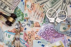 Themis et menottes, marteau sur l'euro et billets d'un dollar Image stock