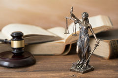Themis statue,books  and gavel on wooden table Royalty Free Stock Photo