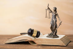 Themis statue on open book and gavel next to it Royalty Free Stock Photos