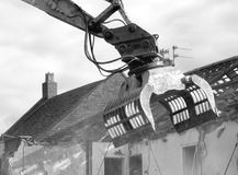 And then it was gone. Black and white monochrome of bulldozer demolition of a pub in England with roof being removed amid Stock Photo