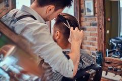 Thendy fryzjer przy nowożytnym zakładem fryzjerskim pracuje na klienta ostrzyżeniu fotografia royalty free