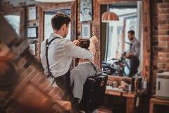 Thendy fryzjer przy nowożytnym zakładem fryzjerskim pracuje na klienta ostrzyżeniu zdjęcia stock