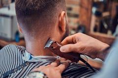 Thendy fryzjer przy nowożytnym zakładem fryzjerskim pracuje na klienta ostrzyżeniu obrazy stock