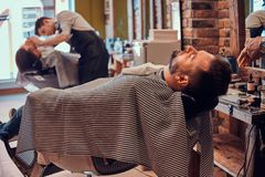 Thendy hairdresser at modern barbershop is working on client`s haircut. Attractive brutal men just got good beardcare from talanted trendy barber stock photos