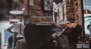 Thendy hairdresser at modern barbershop is working on client`s haircut. Attractive relaxed men just got great service from talanted trendy barber royalty free stock photography