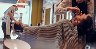 Thendy hairdresser at modern barbershop is working on client`s haircut. Attractive relaxed men just got great service from talanted trendy barber royalty free stock images