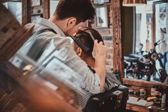 Thendy hairdresser at modern barbershop is working on client`s haircut. Thendy focused hairdresser at modern barbershop is working on client`s haircut royalty free stock images