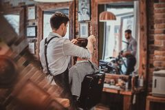 Thendy hairdresser at modern barbershop is working on client`s haircut. Thendy ed hairdresser at modern barbershop is working on client`s haircut stock photos