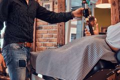 Thendy hairdresser at modern barbershop is working on client`s haircut. Two friends at trendy modern barbershop are celebraiting new beard cut with drinks stock image